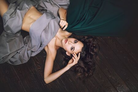 Young beautiful model girl with makeup and hairstyle in flowing fabric lying on wooden floor top view