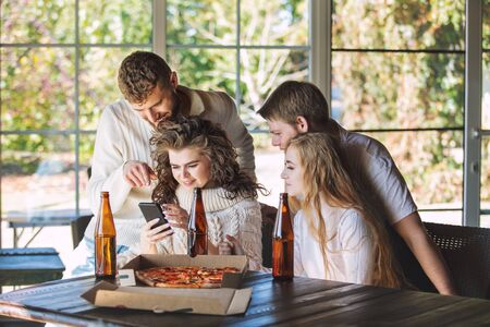 Friends three two men and two women young adults beautiful and happy together with mobile at the table eating pizza and drinking drinks from bottles 版權商用圖片