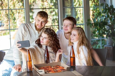 Friends three two men and two women young adults beautiful and happy together with mobile at the table eating pizza and drinking drinks from bottles Фото со стока