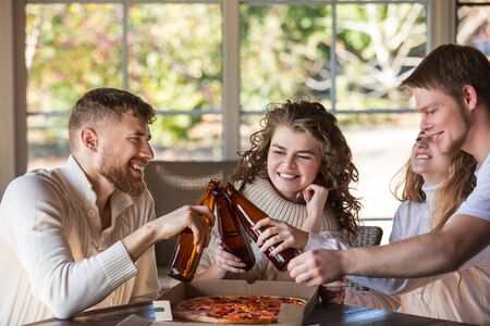Friends four two men and two women young adults beautiful and happy together at the table eating pizza and drinking drinks from bottles Фото со стока - 133137941
