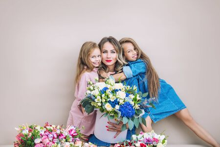 Happy family mother and two beautiful girls daughters on holiday in flowers together on isolated background Фото со стока