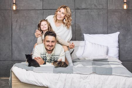 Family father, mother and sweet daughter happy together with little fluffy kittens on the bed in the bedroom in the home interior Zdjęcie Seryjne