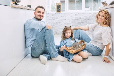 Family father, mother and sweet daughter happy together with little fluffy kittens in the kitchen in a bright home interior