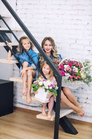 Happy family mother and two beautiful girls daughters on holiday in flowers together in the home interior