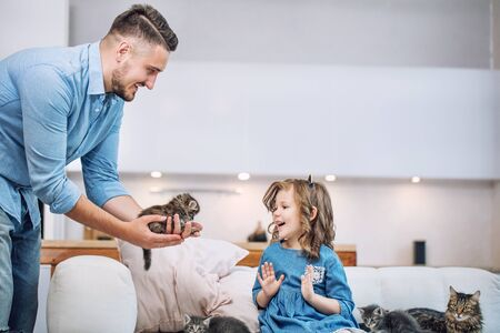 Family, father and sweet daughter happy together with little fluffy kittens in a bright home interior