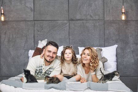 Family father, mother and sweet daughter happy together with little fluffy kittens on the bed in the bedroom in the home interior Фото со стока