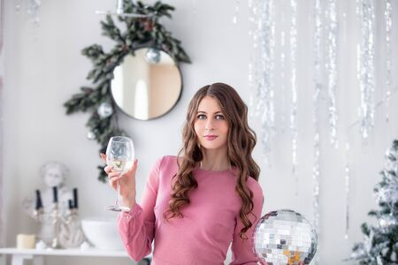 Beautiful happy young woman in beautiful dress with makeup and hairstyle in Christmas decorations