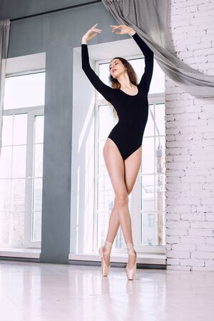 Young beautiful model girl is engaged in ballet in a training bodysuit and Pointe shoes Foto de archivo - 139072707