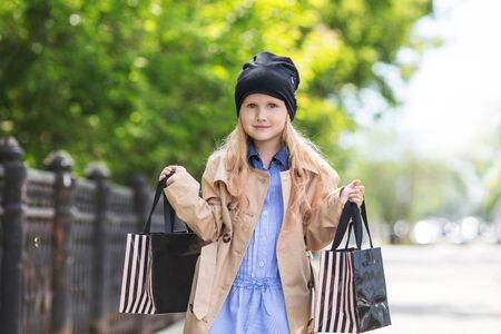 Small and beautiful girl child cute and happy with shopping bags in her hands on the street