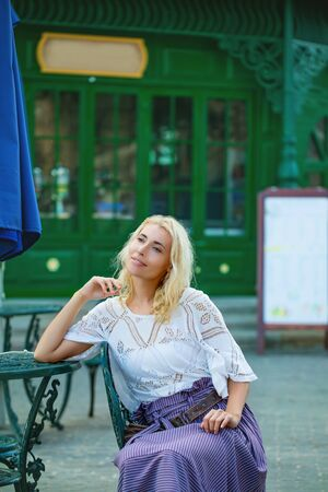 Woman young adult beautiful and happy is sitting at a table in a summer cafe waiting for an order 版權商用圖片