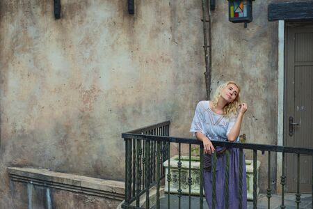Woman young adult beautiful and happy stands on a balcony against an old wall 版權商用圖片