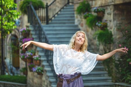 Woman adult young beautiful and happy blonde on the background of stairs on the street of a European city 版權商用圖片