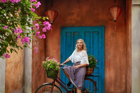 Woman young adult beautiful happy on a Bicycle in the background of the door to the house 版權商用圖片