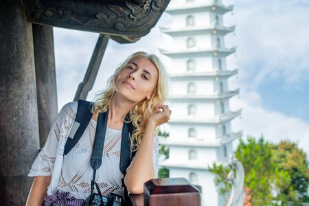 Female tourist young adult beautiful against the background of a white Buddhist temple