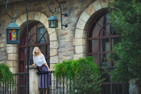 Woman an adult young beautiful and happy blonde on the balcony of an old beautiful European house