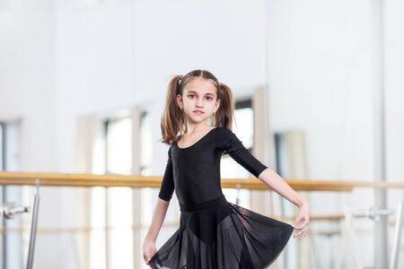Small beautiful sweet girl child in the studio trains for a dance lesson.