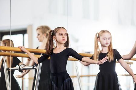 Small beautiful cute girls children in the Studio train with a coach at a dance lesson. Zdjęcie Seryjne