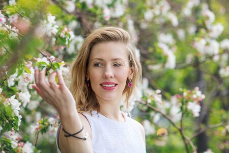 Beautiful young and happy woman close-up portrait on the background of a blooming Apple tree