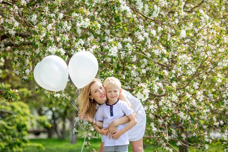 Family mother and son, beautiful and happy with balloons on the background of a blooming Apple tree Zdjęcie Seryjne