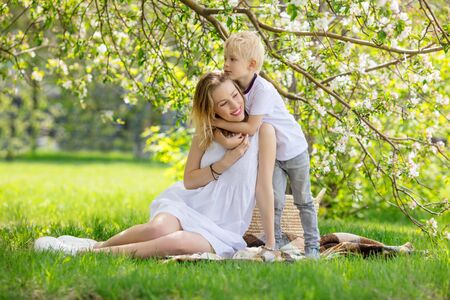 Family mother and son, beautiful and happy together sitting on the grass in front of a flowering Apple tree 版權商用圖片
