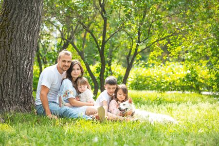 Happy beautiful big family together mother, father, children and dog walking on a Sunny summer day 版權商用圖片