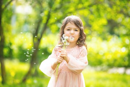 Little girl child cute and beautiful with a bunch of dandelions blowing on them in nature