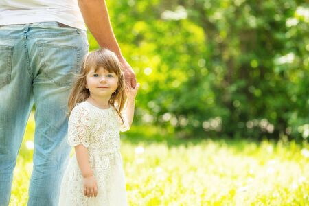 Portrait of a beautiful little girl walking hand in hand with her father close-up