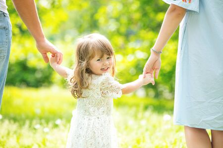 Portrait of a small beautiful girl child walking hand in hand with her parents close up