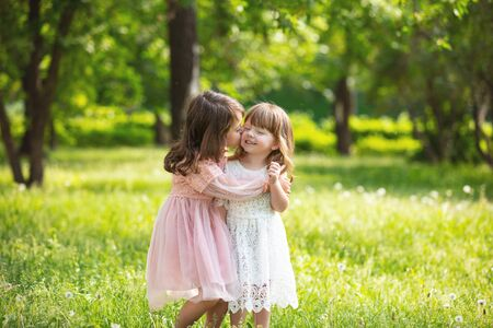Two small beautiful girls children together happy play and laugh in nature 版權商用圖片