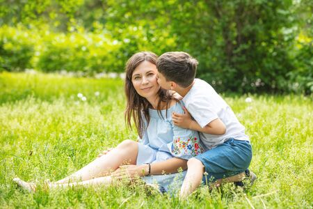 Happy beautiful family together mother and son portrait on the grass on a Sunny summer day