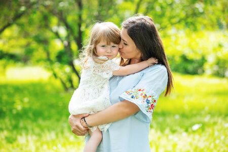 Happy beautiful family together mother and daughter portrait on the grass on a Sunny summer day