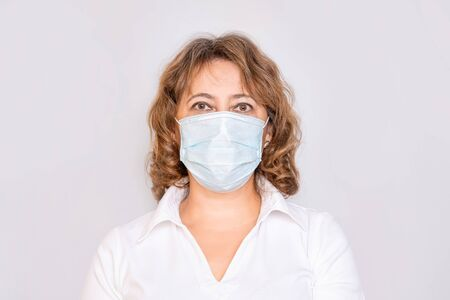 Portrait of a woman adult elderly in a medical mask on an isolated background