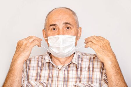 Portrait of a man an adult elderly pensioner in a medical mask on an isolated background
