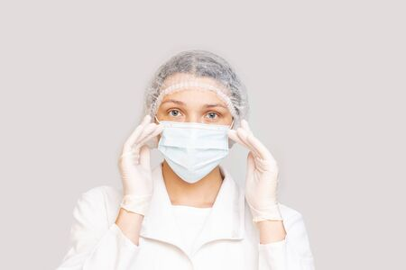 Portrait of a woman adult young in a medical mask, gloves and cap on an isolated background
