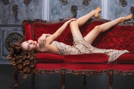 Beautiful luxury young girl model on a vintage sofa in a magnificent interior 版權商用圖片