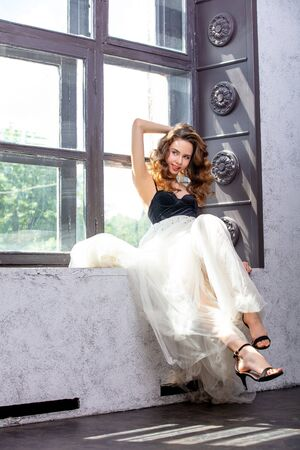 Beautiful luxurious young girl model with makeup and brown curls on the window in an airy skirt