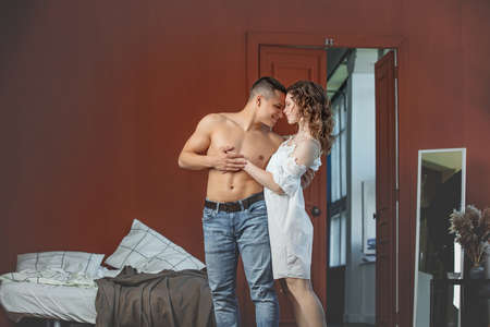 Young adult beautiful couple in love, man and woman together in bedroom home interior 写真素材