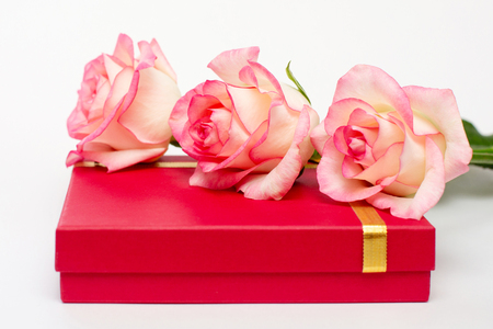 Three roses lie on the red bass box. Gifts on a white background. A gift for the beloved. Your gifts.
