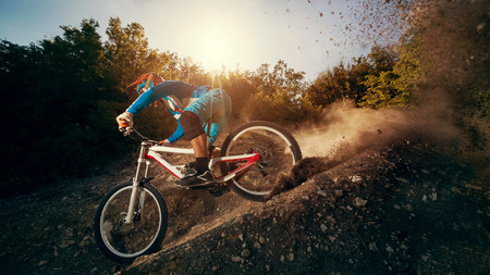 bicycles: Downhill mountain bike. Young man cyclist to riding a bicycle. Stock Photo