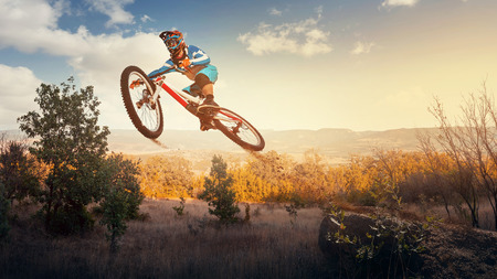 trick: Man high jump on a mountain bike. Downhill cycling. Stock Photo