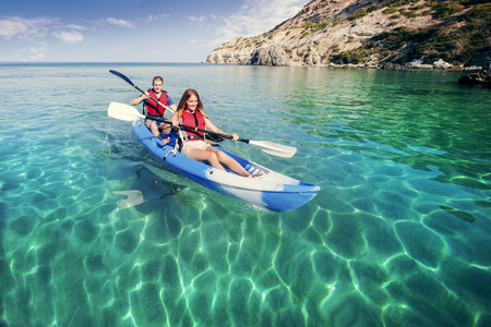 Sailing on the sea kayaking. Young happy couple traveling by kayak. Activities on the water.