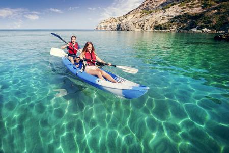 canoa: Navegando en el kayak de mar. Feliz pareja joven que viaja en kayak. Actividades en el agua.