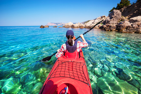 Two men paddle a kayak on the sea. Kayaking on island Stock Photo