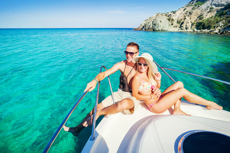 recreation yachts: Romantic happy couple in love relaxing on a yacht at sea. Man and woman lying and hugging on a private boat cruising on the islands. Luxury holidays on the water.