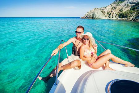 donna ricca: Romantica coppia felice in amore rilassante su uno yacht in mare. L'uomo e la donna che si trova e abbracciare su una barca privata crociera sulle isole. Vacanze di lusso in acqua.