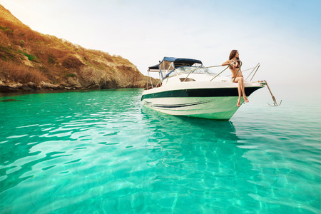 swimwear: Beautiful young woman recreation on the boat a sunny summer day. Luxury vacation at sea.