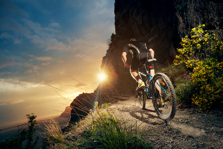bike wheel: Cyclist riding mountain bike on trail at evening.
