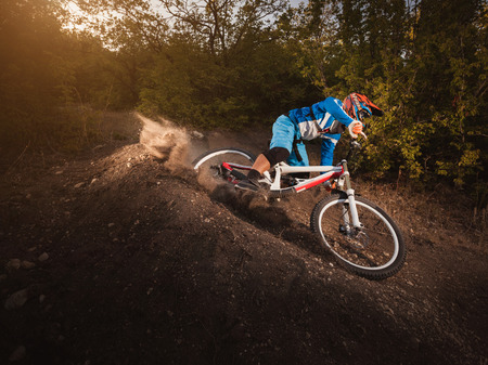 Mountain Bike cyclist riding forest track at sunrise healthy lifestyle active athlete. Downhill biking. Standard-Bild