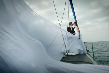 destination wedding: Happy bride and groom on a yacht.