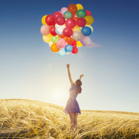 Girl running on the field with balloons at sunset. Happy woman on nature.